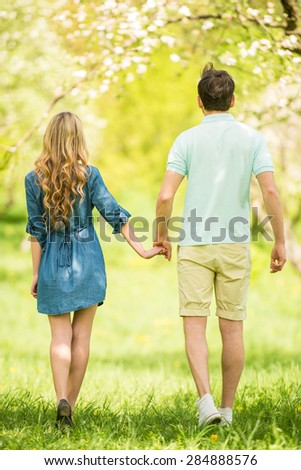 Young beautiful couple dressed casual having fun in summer park. - stock photo