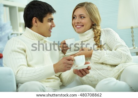 Young beautiful couple drinking tea at home