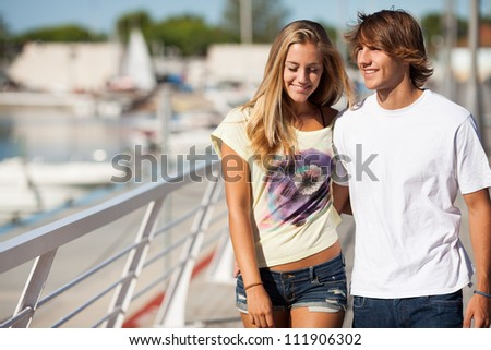 Young beautiful couple enjoying a walk by the harbor