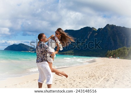 Young beautiful couple enjoying beach getaway. Couple in love, summer luxury vacation in Hawaii. Travel holidays concept.