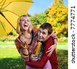 young beautiful couple have fun under yellow umbrella - stock photo