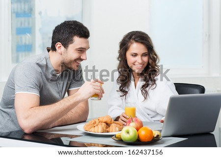 young beautiful couple having breakfast with a laptop - stock photo