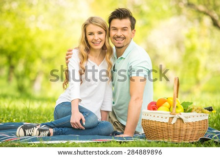 Young beautiful couple having picnic on the lawn in summer park. - stock photo