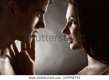 Young beautiful couple in each other's arms on a dark background - stock photo