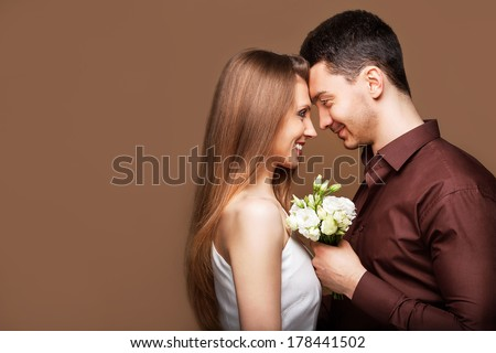 Young beautiful couple in love looking at each other, the concept of the wedding, the newlyweds holding a bouquet of flowers. Valentine's Day - stock photo