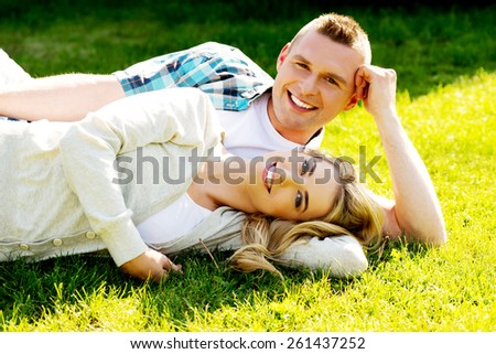 Young beautiful couple in love lying on the grass - stock photo