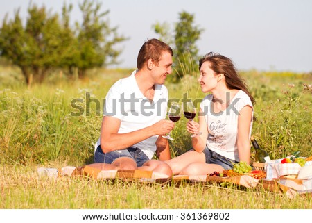 Young beautiful couple in love relaxing on a picnic in the countryside