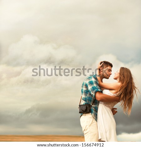 Young beautiful couple in love standing together in summer evening in countryside on the corn field. Handsome man posing with his blonde girlfriend.  - stock photo