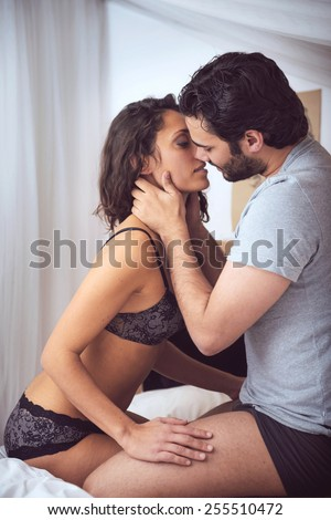 Young beautiful couple in sensual games in bed - stock photo