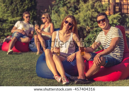 Young beautiful couple in sun glasses is holding bottles of beverage and smiling, sitting on bean bag chairs outdoors. In the background the other couple is talking
