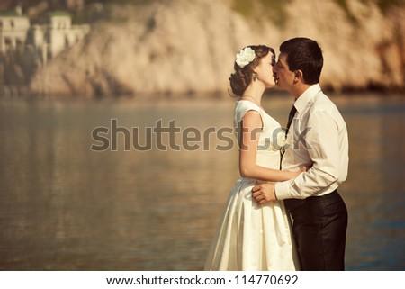 Young beautiful couple kissing at the sea. Wedding kiss. - stock photo