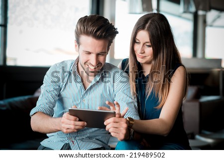 young beautiful couple lovers at the cafe using tablet - stock photo