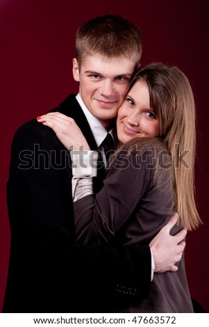 young, beautiful couple on a dark red background - stock photo