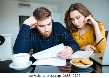 Young beautiful couple reading their bills at home