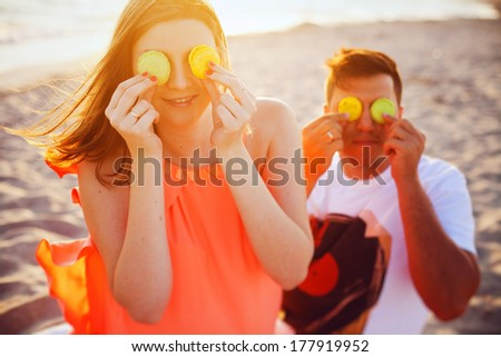 Young beautiful couple relaxing on the beach and eats macarons - stock photo