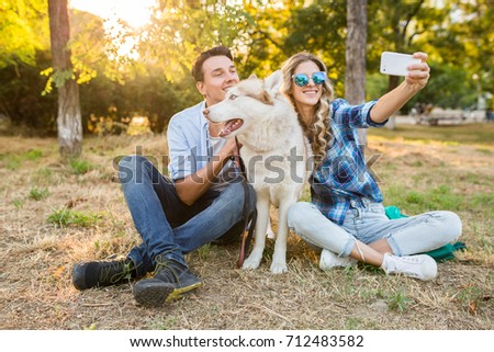 young beautiful couple sitting in park, smiling, happy friends together, casual denim outfit, summer style, making selfie photo with a husky dog, having good time