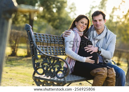 Young Beautiful Couple sitting on a Bench in the Park in sunset lights, woman pregnant, outdoor - stock photo