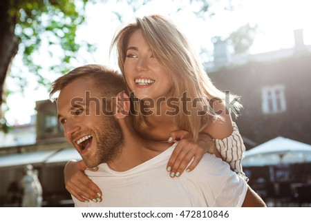 Young beautiful couple smiling, embracing, walking in park.