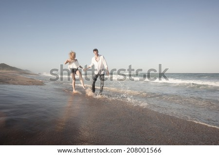 Young beautiful couple splashing each other with water at the beach