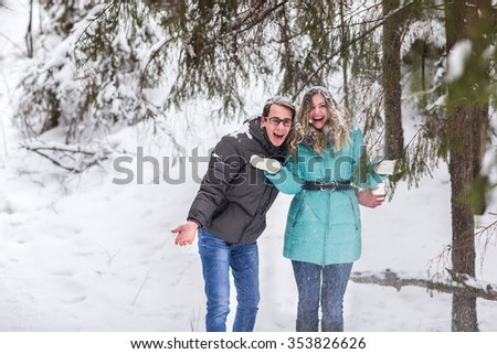 Young beautiful couple walking in winter forest. Couple playing with snow in winter in a park.