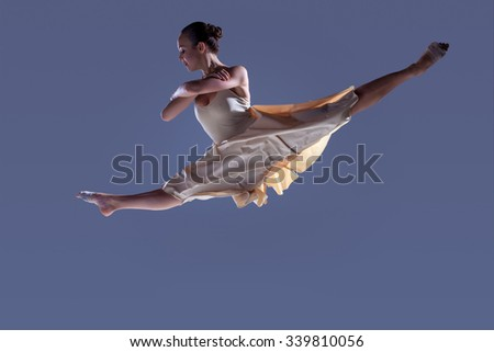 Young beautiful dancer in beige dress jumping on gray studio background - stock photo
