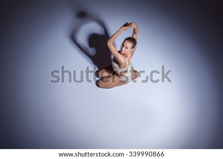 Young beautiful dancer in beige swimwear dancing on lilac floor background