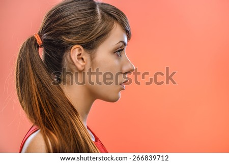 young beautiful dark-haired calm woman in profile, on red background - stock photo