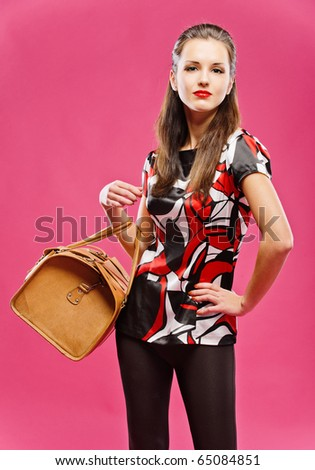 Young beautiful dark-haired girl has control over leather brown bag, on red background.