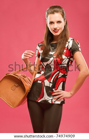 Young beautiful dark-haired girl standing with a large brown leather bag, on a red background