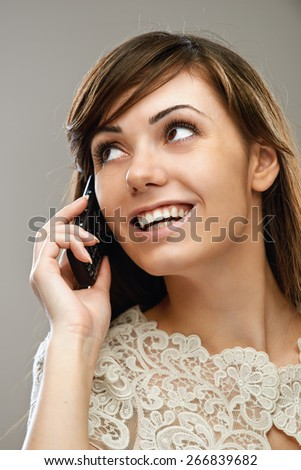 young beautiful dark-haired smiling woman talking on mobile phone, on gray background - stock photo