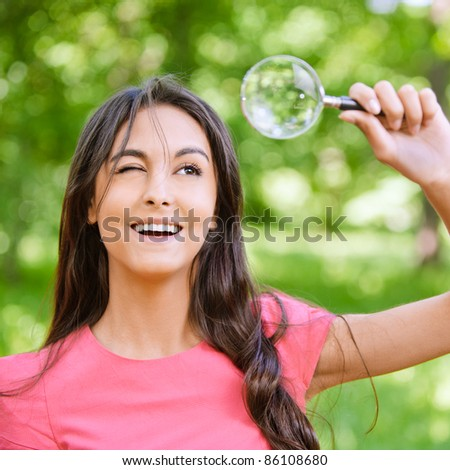 Young beautiful dark-haired woman in red dress looks through magnifier and smiles, against green summer garden. - stock photo