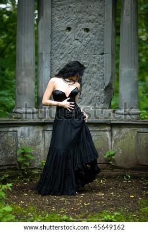 Young beautiful demonic female creature walking through the night - stock photo