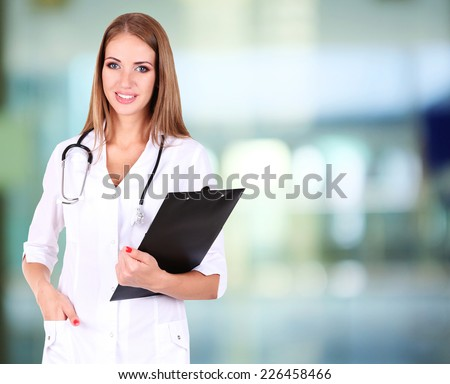 Young beautiful doctor holding folder on hospital background - stock photo