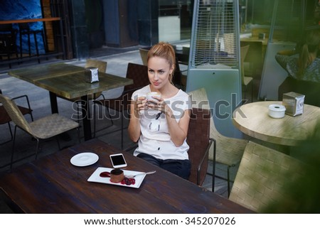 Young beautiful dreamy woman drinking cappuccino while sitting alone in modern coffee shop, charming lady thinking about something while enjoying leisure during morning breakfast in cozy cafe bar  - stock photo
