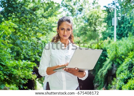 Young Beautiful East Indian American Woman traveling, working in New York, wearing white shirt, holding laptop computer, walking at Central Park. Street bridge with green leaves on background.