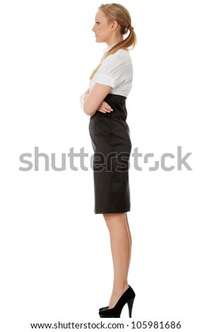 Young beautiful elegant businesswoman is standing sideways with crossed hands. Isolated on the white background. - stock photo