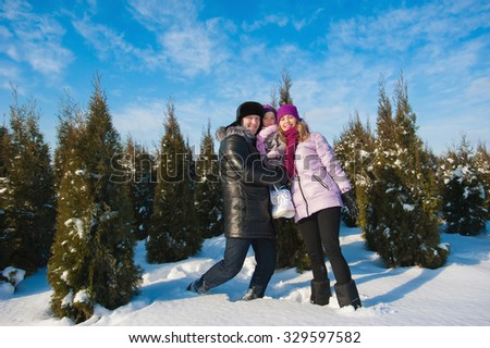Young beautiful family in bright clothes choosing a Christmas tree, snow, lifestyle, winter holidays - stock photo