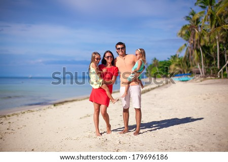 Young beautiful family of four enjoyed relaxing on the beach - stock photo