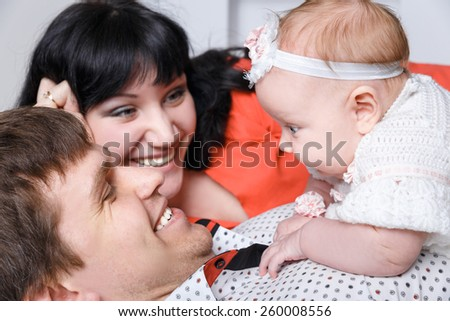 Young beautiful family of 3 persons Mum, Dad and little daughter posing in the studio - stock photo