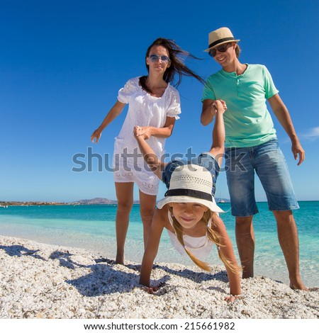Young beautiful family of three have fun on tropical vacation - stock photo