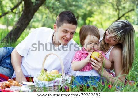 Young beautiful family of three on a picnic - stock photo