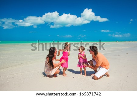 Young beautiful family with two daughters having fun at beach