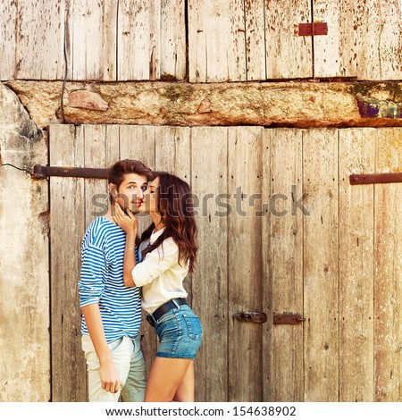 Young beautiful fashion couple in love having fun outdoor in summer. Girl kiss surprised boy. - stock photo