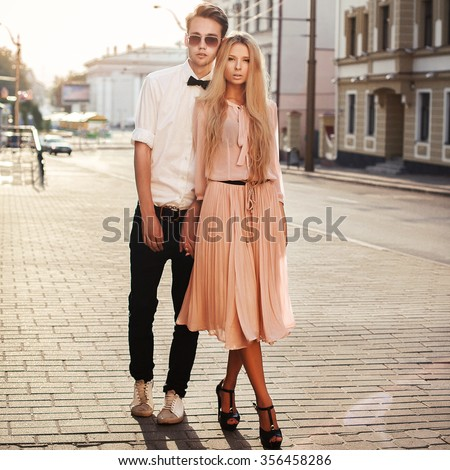 Young beautiful fashion hipster couple in love posing outdoor on the street standing together  - stock photo