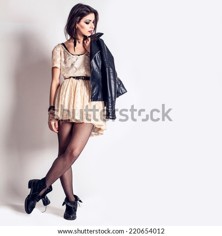 Young beautiful fashion model with professional makeup. Rock and punk style. Stylish dress,leather jacket and boots. woman - stock photo