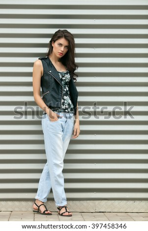 Young beautiful fashionable brunette woman in black leather jacket posing outdoors against urban style background of metal strips - stock photo