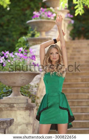 Young beautiful fashionable girl model in fashion green dress posing on stairs over blossom park background.  - stock photo