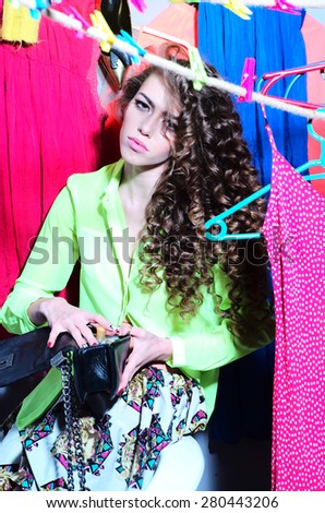 Young beautiful fashionable strange woman with curly hair sitting amid colorful dresses red blue pink green yellow colors and holding little bag, vertical picture