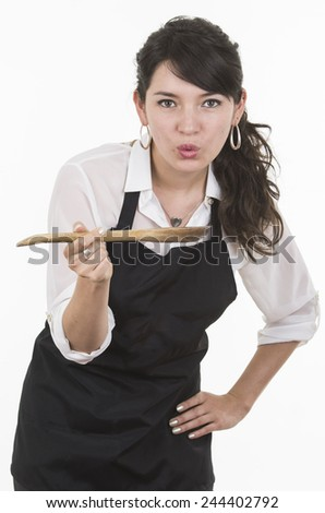 young beautiful female chef wearing black apron holding wooden spoon with hot food isolated on white - stock photo