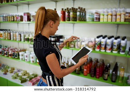 Young beautiful female consultant checks the quality of cosmetic product verifying information on digital tablet, woman entrepreneur puts pharmaceutical production on trade shelves in her drugstore  - stock photo